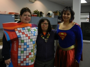 Three librarians in Halloween costumes: scrabble board, witch, superwoman